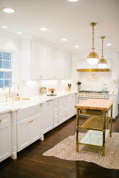 White kitchen with gold accents, butcher's block top island and animal print rug | Hemingway & Hepburn
