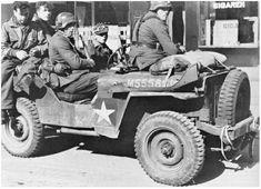 Met buitgemaakte jeeps worden krijgsgevangenen afgevoerd