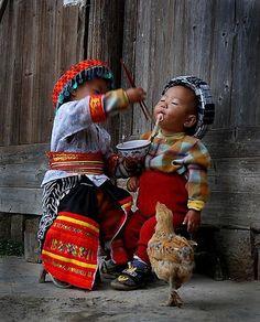 Tyttö syöttää pojalle nuudelia. (Kiina)