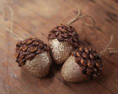 Acorn Ornaments, Champagne, Set of 3 A set of 3 acorn ornaments. These acorn ornaments are handmade with real pine cone pieces, hollow mache cores, and two colors of beautiful crystalline glitter. The