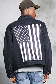 A distressed denim jacket featuring a back satin patch with a black-and-white American flag graphic, a button front, basic collar, long sleeves with button cuffs, button-flap chest pockets, and slanted front pockets.