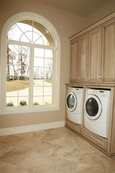 "I like the idea of the washer & dryer up in a ""cabinet"" like this, easier to clean... Beautiful custom laundry room cabinets from Classic Industries"