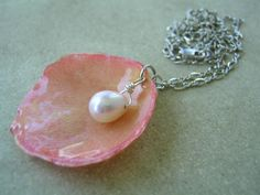 Preserved rose petal with pearl... looks like a seashell. Might try to figure out how to do this with the necklace from my wedding and one of the rose petals.