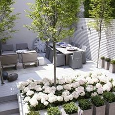 Varanda com flores no jardim, mesa e cadeiras em vime com 8 lugares e poltronas externa, piso branco.