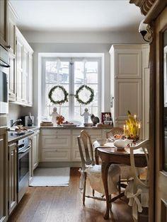 Ett kök som lika gärna kunde finnas på en stor lantgård. Köksinredning i cremefärg från Carin & Carl. Matbord och stolar i rokoko respektive gustaviansk stil. Kransarna i hemmet, av olivkvistar och mjuk en, är bundna av floristen Camilla Ek.