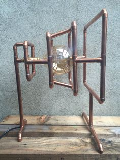 A beautiful one off lamp made from copper pipe, All of the joints have been soldered to give it a very strong frame. i have polished all of the copper to give it a nice shine but its not lacquered so if you leave it to tarnish it takes on a whole new look. Bulb included Hight 19 Depth 13 First square 11 3/4