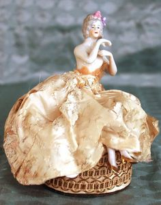 Vintage French Powder Box with Porcelain Figurine A very demure and charming young lady daintily sits atop a box made by the very old and established perfume manufacturer, Houbigant. The box dates from 1920-1930