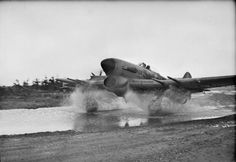 A Hawker Typhoon Mark IB of No. 439 Squadron RCAF taxies through a water splash at B78/Eindhoven, Holland, while leaving its dispersal loaded with two 1,000-lb bombs for an attack on a rail target behind the German lines.