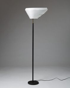 Shade white painted steel. Base and shaft covered with black leather. Polished brass fittings. H: 167 cm/ 5' 5 3/4''