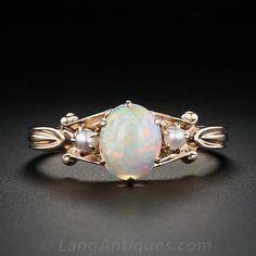 This is a sweet and petite Victorian style ring in 10 karat rose gold. A .65 carat oval cabochon white opal is set with pointed prongs and highlighted by small seed pearl accents.