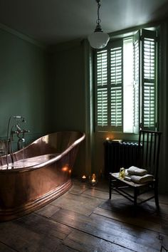 Romantic and rustic green master bath with a freestanding copper bathtub.