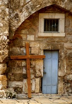 """Jerusalem, Israel. This small door with the cross beside it was to the right of the main entrance to the Church of the Holy Sepulchre."""