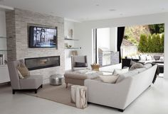Amazing family room with stacked glass floating shelves over floating white lacquer cabinets flanking floor to ceiling fireplace with flatscreen TV