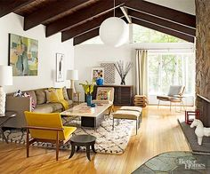 The new homeowners had red oak floors installed in the living room to match the home's other rooms. Luckily, other architectural details -- hefty ceiling beams, windows that follow the roofline, and a massive three-sided rock fireplace -- had not been altered. The couple's mix of vintage and modern furnishings feels just right in the vintage-inspired living room./