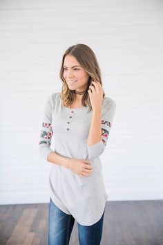 The Peek A Boo Heather Grey Floral Top is the perfect top to bring in the spring season and adds the perfect amount of pop of color to any wardrobe.Our Peek A Boo Heather Grey Floral Top is airy, and light and has a fabulous button accent with the fabulous peek-a-boo floral detail. This top could not be more perfect for pairing with your favorite Bermudas and sandals this summer or spring. || Bella Ella Boutique    Peek A Boo Heather Grey Floral Top Bella Ella Boutique Online Store