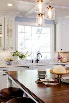 wooden island, marble counters, glass in door cabinets and awesome tile