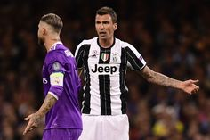 Juventus' Croatian striker Mario Mandzukic (R) clashes with Real Madrid's Spanish defender Sergio Ramos during the UEFA Champions League final football match between Juventus and Real Madrid at The Principality Stadium in Cardiff, south Wales, on June 3, 2017. / AFP PHOTO / JAVIER SORIANO