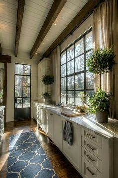 love alot of what is going on here: darker antique wood floors, dark beams with ship lap between, black window, light cram colors
