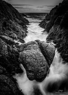A black and white photograph of the rushing waves around a boulder along the coastline of Sambro, Nova Scotia.