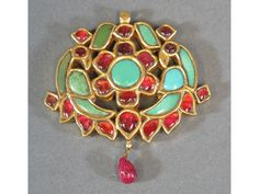 A GEM-SET GOLD PENDANT Southern India, 20th century  set with turquoise, garnet and foiled rubies, in the form of an openwork floral medallion, flanked by birds, repousse decoration on the reverse  5 x 4.8cm