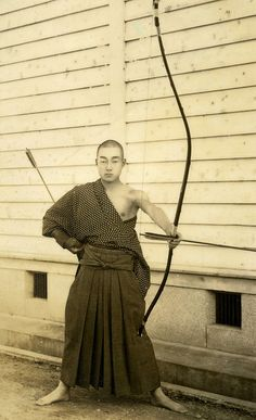 Kyudo - Way of the Bow 1930s    The Yumi (Japanese Bow) is an asymmetrical longbow over two metres in height that is traditionally made of bamboo, wood and leather, while the Ya (arrows) of this period have bamboo shafts with eagle or hawk feather fletchings. Practiced for centuries as both a Gendai budo (Martial Art) and a form of Zen meditation, the sport of Kyudo is still widely studied throughout Japan.