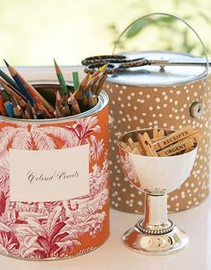 Tin cans and paint buckets wrapped in colorful scrapbook papers or fabric become inexpensive stylish holders for pencils, pens, or paintbrushes.