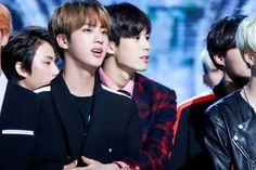 Hongbin (vixx) has his arms around Jin (BTS)