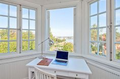 How wonderful to work in a nook surrounded by windows and a lovely view of greenery and water.
