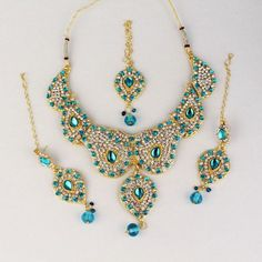 """This is a beautiful Designer Kundan Jewelry set in dark Turquoise (Ferozi) color with Kundan stones and shining diamonds on Gold plated base with hanging beads. The necklace and the entire set has high quality CZ diamonds, hanging tassels and beads at the end.    Contents: Necklace, Pair of earrings and Maang tikka    Base: High Grade Alloyed Metal.    Size:Necklace: White/Blue Stones Length 30"""", Pendant 2.5"""", Earring 3"""", Maang Tikka 6""""    Rs. 850"""