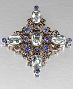 AQUAMARINE AND SAPPHIRE BROOCH/PENDANT, CHILD & CHILD AND A PERIDOT AND DIAMOND BROOCH/PENDANT, 1900'S Of open work scrolled design in the form of a stylised Greek cross, set to the centre and to the cardinal points with oval- and cushion-shaped aquamarines.