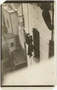 Djuna Barnes and unidentified fireman, dangling from a rope beside a building, October 1914. 6 1/4 x 3 3/4 in. (15.9 x 9.5 cm), Djuna Barnes Papers, Special Collections, University of Maryland Libraries
