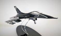 This three-dimensional sculpture of an F-16 Falcon Fighter is armed with rockets and ready for combat.  It is manufactured from laser-cut high quality acrylic glass and lovingly hand assembled. This exquisite fighter jet comes in black with clear, transparent edges, which give it a great sparkle, and with clean engraved details. It is a must have for fighter-jet lovers, pilots and aviators.  This specific F-16 was originally designed as a gift for the commander of a specific F-16 squadron in…