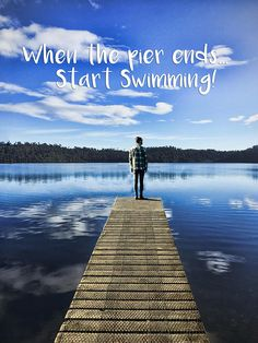 """Decorate your home or office with gorgeous nature photographs that also deliver powerful life messages.This image shows a crystal blue lake with a person standing at the end of the pier. Quotation """"When the pier ends, start swimming"""" (inspirational,quotation,sayings,motivational,perseverance,lake,person,pier,hope,inspiration,inspire,motivation,motivate,quote,sun,photography,nature,outdoors,attitude,positive,outlook,possibilities,clouds,beautiful,)"""