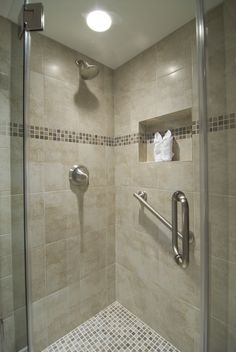 Oliva Oceano Mosaic accents the shower wall tiled in Crema Pavia Antica. #bathroom #shower