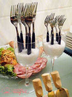 Facilite a vida dos seus convidados deixando talheres à disposição. Uma forma de fazer isso é colocá-los em pé em taças cheias de sal grosso.