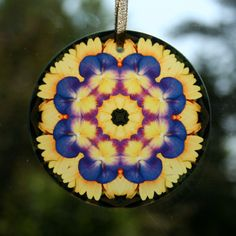 Glass suncatcher adorned with my purple pansy on a yellow daisy boho chic mandala new age sacred geometry kaleidoscope design tilted Blissful Beliefs. <br /> <br />This stunning pansy beveled glass suncatcher illuminates my geometric mandala kaleidoscope design when light shines through it! It is 3 - ½ inches in diameter and has a beveled edge. The suncatcher ...