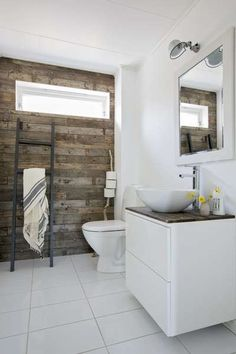 Treveggen på toalettet er laget av gamle, naturslitte planker som de fant på eiendommen. Skapet under vasken fra ikea har de laget av en gammel skjenk. På veggen henger en Jielde-lampe.