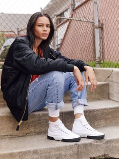 Binx Walton wears distressed denim with a black jacket, a red T-shirt and white high-top sneakers.