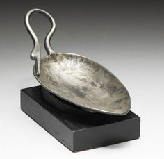 A Roman silver spoon  Circa 4th Century A.D. With a large ovoid bowl, the short looped handle terminating in a swan head, the long bill resting on the side of the bowl, the details of the feathers and eye incised, the beak slightly open, 5in (13cm) long, mounted