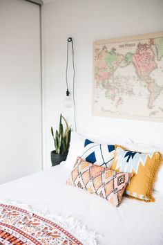 Bedroom look- super simple- white walls and duvet with colorful pillows and vintage map with a little green