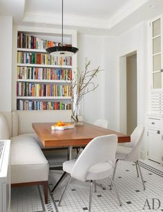 Michael J. Fox and Tracy Pollan's Manhattan Home : Architectural Digest. In the breakfast room, the Lightolier pendant lamp and the table, a teak partners desk by Florence Knoll, are both from Wyeth; the banquette is covered in a Lee Jofa linen, Kitchen Nook, Kitchen Dining, Banquette Seating In Kitchen, Built In Dining Room Seating, Kitchen Bookcase, Kitchen Booths, Corner Seating, Corner Bench, Floor Seating