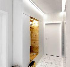 PRZEDPOKÓJ. Zarówno z zewnątrz, jak i od wewnątrz zabudowę oświetlają listwy LED. Zainstalowano je pod sufitem oraz we wnęce i w wysokich zamykanych szafkach. Trudniej dostępne górne schowki są przeznaczone na rzadziej używane rzeczy.