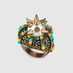 A metal ring with a center glass pearl embedded with spikes, colored beads decorate the sides.