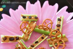 Ants and butterflies on a log using peanut butter, raisins and pretzels.