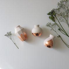 Estos supersimpáticos floreros hechos de porcelana y cobre, de aquí.