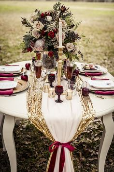 fall wedding table setting with a gold table runner and burgundy glasses…