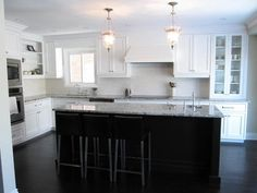 kitchen with white cabinets, dark island, dark hardwood floors
