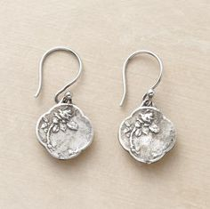 """Rosa rugosa, the rambling cousin of the world's most romantic flower, finds a home on dangling charms of antiqued cast sterling silver designed by Adriana Goddard. 1""""L."""