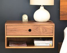 Our Floating Nightstand is Mid-Century Modern inspired and is built by hand from solid Black Walnut, grown and milled domestically. It mounts easily to your wall using a French cleat (Included) for a beautiful floating appearance. (see links below for smaller sizes as well as options for no drawer)  Each piece is built from solid hardwood boards joined with a 45 degree miter creating a beautiful wrap-around continuous grain.  The drawers are built from solid Birch with a hardwood front to…