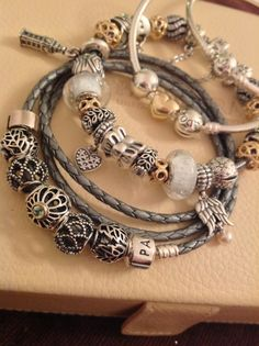 PANDORA Trio of Bracelets, with Silver, Braided Leather and Bangle, Showcasing Stunning Mix of Silver and Gold Charms.